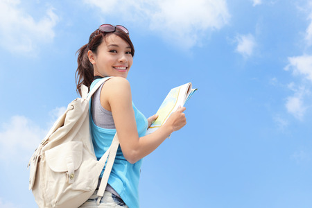 Happy travel woman look map and look to you with sky background, asianの写真素材