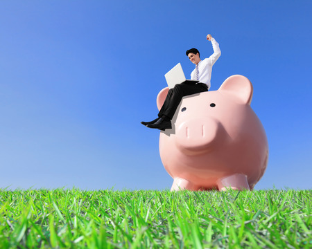 Happy Saving Money with my piggy bank - Young business man sitting on piggy bank with computer