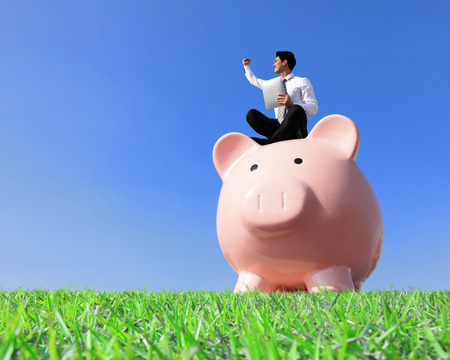 Happy Saving Money with my piggy bank - Young business man sitting on piggy bank with touch pad