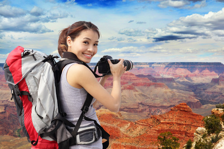Young woman with backpack taking a photo in grand canyon, asian