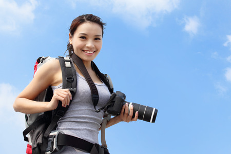 Young woman mountain hiker holding camera with sky background, asian