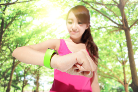 Photo pour Health sport woman wearing smart watch device with touchscreen doing exercises with green tree background, focus on watch, asian - image libre de droit