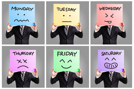 Day of week and face expression - Young business man holding blank billboard card displaying face expression isolated on gray background