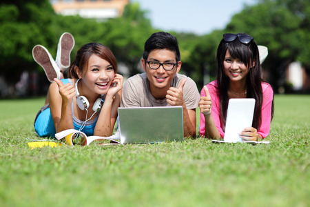 Happy College students using laptop and tablet pc on campus lawn, asianの写真素材