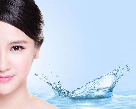 Beauty Skin care concept, Beautiful woman face with Water splashes isolated on blue background, asian modelの写真素材