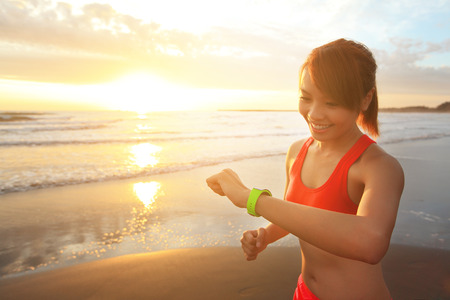 Photo pour Health sport young woman run and look wear smart watch device with touchscreen on the beach at sunrise, asian - image libre de droit