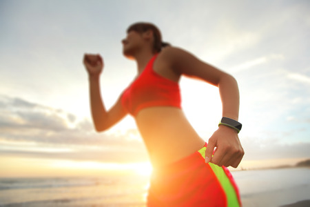 Photo pour Health sport young woman run and wear smart watch device ( focus on watch ) on the beach at sunrise, asian - image libre de droit