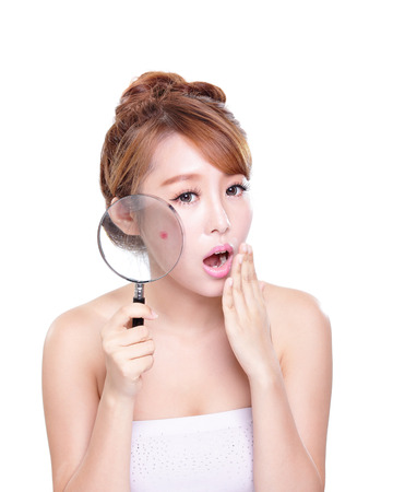 young woman with a acne and magnifying glass check it isolated, concept for skin care, asian