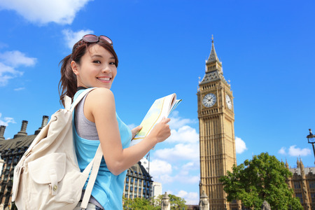 Happy woman travel in London with Big Ben tower, she look map and smile to you, asian