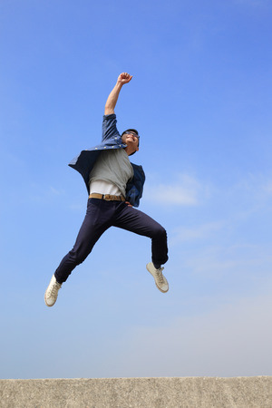 Photo pour Happy College student man run and jump with blue sky background, full length, asian male - image libre de droit