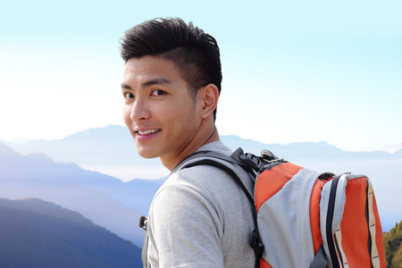 Successful man mountain hiker with backpack on the top of mountains. asianの写真素材
