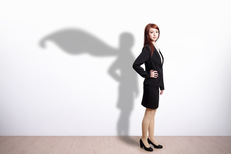 Foto de Superhero Business Woman with white wall background, great for your design or text, asian - Imagen libre de derechos