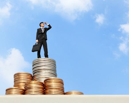 Photo pour I want be rich - Successful business man stand on money with blue sky, asian male - image libre de droit