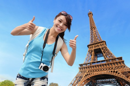 Happy travel woman in Paris with Eiffel Tower and she show thumbs up