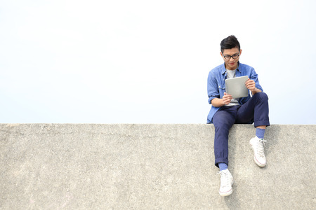 Happy College student man using digital tablet pc and sit, asian male