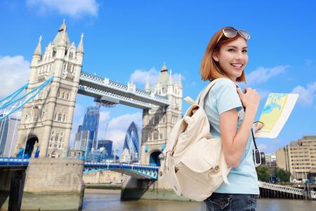 Photo pour Happy woman travel in London with tower bridge, and smile to you, caucasian beauty - image libre de droit