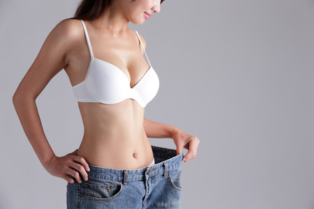 Photo pour woman shows weight loss by wearing old jeans, asian beauty - image libre de droit