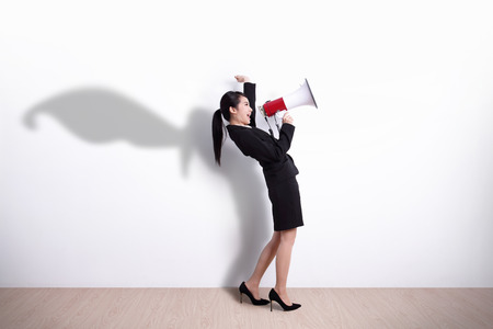 Superhero business woman talking in megaphone with white wall background, great for your design or text, asian