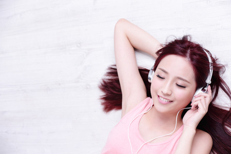 Photo pour Young woman enjoying the music and relax lying at home, asian beauty - image libre de droit