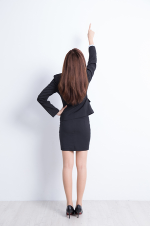 Photo pour Back view of business woman pointing white wall background, great for your design or text, asian - image libre de droit