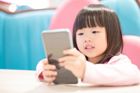 Foto per child girl happy look smart phone. asian child - Immagine Royalty Free