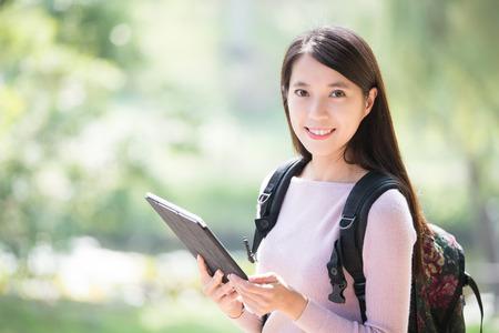 Foto de young woman student smile with digital tablet. nature green background, asian beauty - Imagen libre de derechos