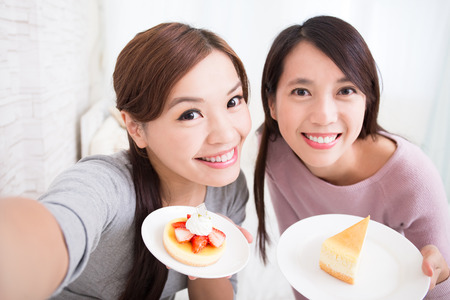 Two happy young female friends take selfie picture with coffee cups and cakes in the living room at home, asian beauty