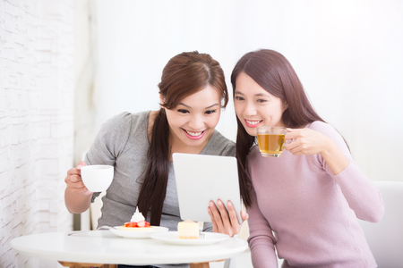Two happy young female friends use digital tablet pc with tea, coffee and cakes, healthy lifestyle and tecnology concept, asian beauty