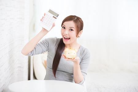 Photo pour smile young woman hold calculator and piggy bank at home, business concept, asian beauty - image libre de droit