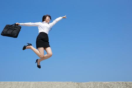 Foto de Successful business woman jump and run with blue sky background, full length, asian - Imagen libre de derechos