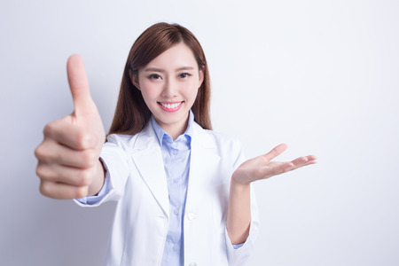 Foto de Smiling dentist woman thump up and show something. with white background. asian - Imagen libre de derechos