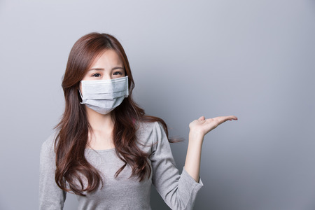 A Woman wears a mask and show something, illness, asian beauty,gray background
