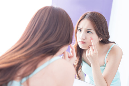 Face Skin Problem - skin care woman unhappy touch her acne and look mirror. asian beauty
