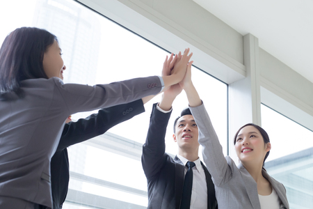 Foto de Business people team smile give high five in the office, shot in Hong Kong, asian woman and man - Imagen libre de derechos