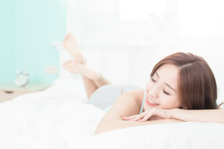 Foto de Health woman Smile feel carefree and she lying on the bed in the morning , asian girl - Imagen libre de derechos