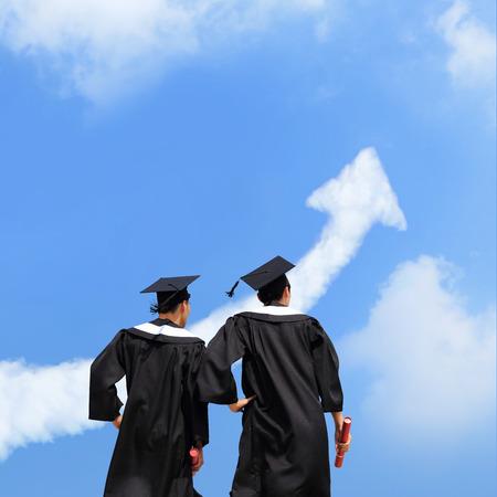 Foto de Back view of graduates student look arrow cloud in blue sky and think future - Imagen libre de derechos