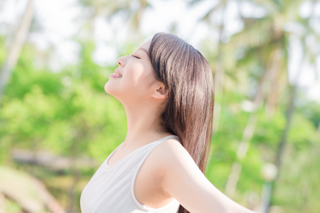 Photo for young woman raising her arms and smile to you, nature green background - Royalty Free Image