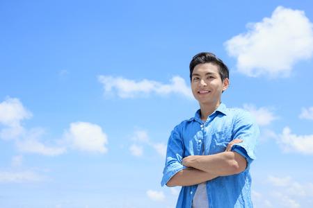 Photo pour man smile happily to you with blue sky, asian - image libre de droit