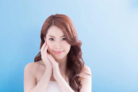 Photo for Beauty woman with charming smile to you with isolated blue background, asian - Royalty Free Image