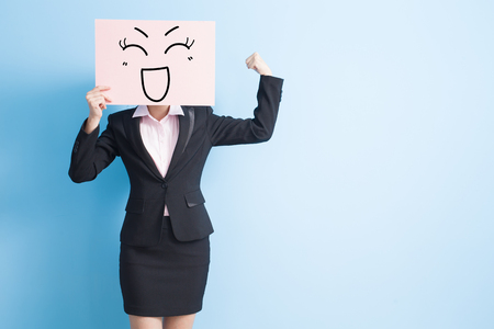 Foto de business woman take happy billboard and make a fist, isolated blue background - Imagen libre de derechos