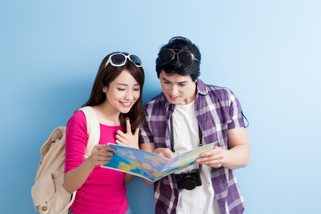 young couple take map and smile happily isolated on blue background