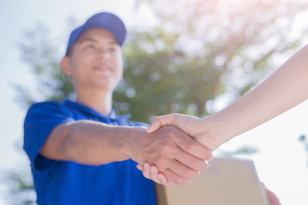 Photo for deliveryman stand and shake hand, asian - Royalty Free Image