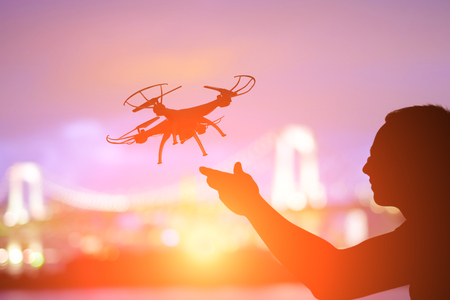 Photo pour silhouette of man play drone in the sunset with odaiba - image libre de droit