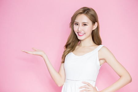 Photo pour beauty skincare woman show something to you on the pink background - image libre de droit
