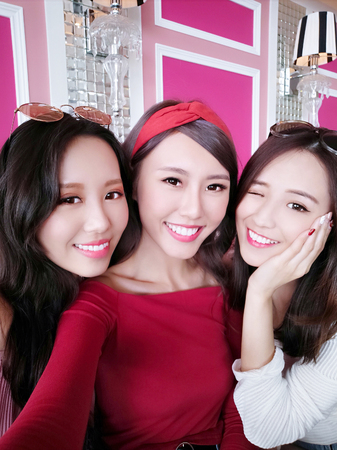 three beauty woman selfie happily in the restaurantの写真素材