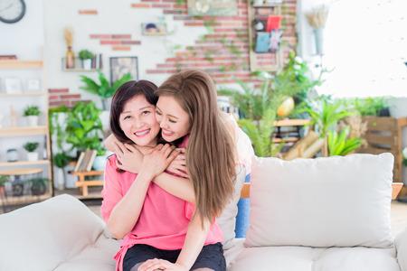 Foto de daughter give her mother hug and smile happily at home - Imagen libre de derechos