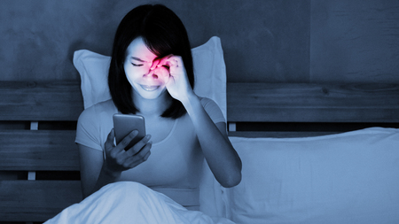 Photo for woman use phone with eye problem on the bed at night - Royalty Free Image