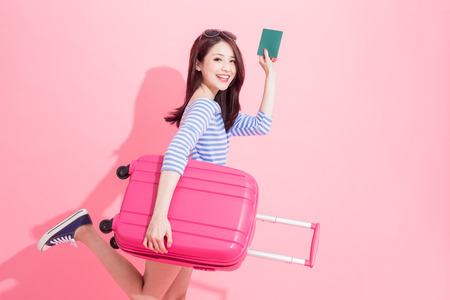 woman take luggage case and passport with travel concept