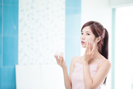 beauty woman with moisturizer concept in the bathroom