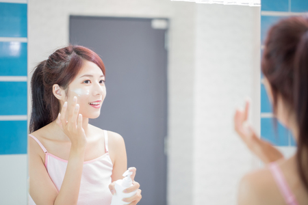 beauty woman apply lotion on her face in the bathroom